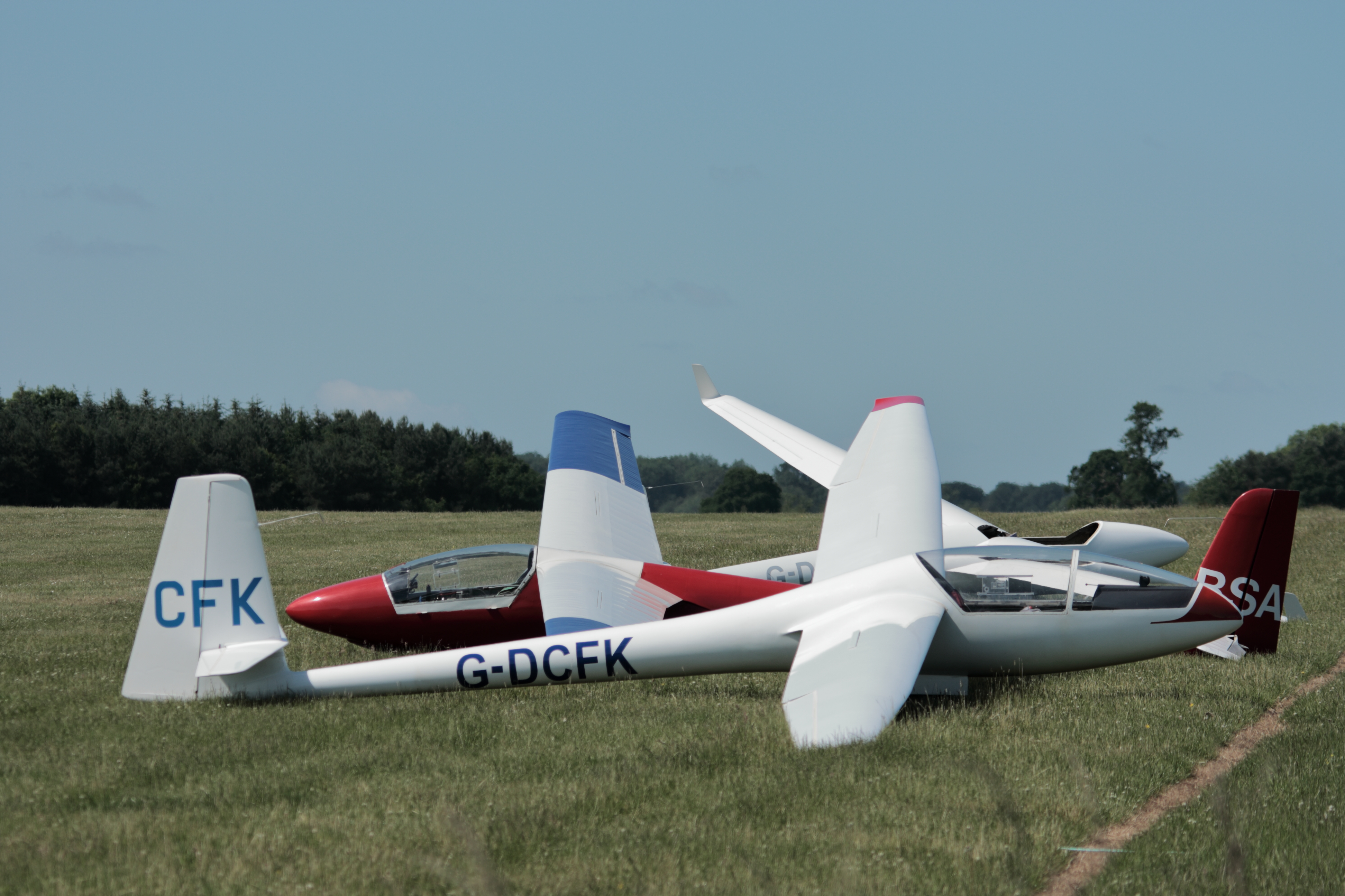 image od gliders at rest on a grass airfield